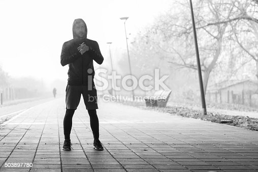 Black and white shot of a man running on a misty morning.