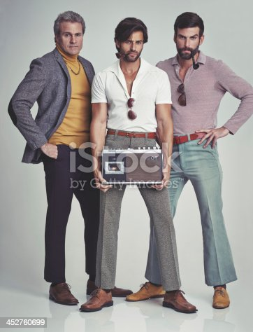 A studio shot of three men clad in retro 70s wear holding a cassette player