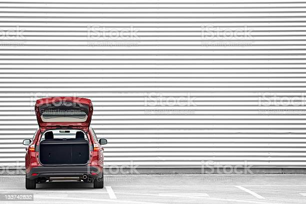 Red station wagon with trunk opened parked before a shopping mall wall