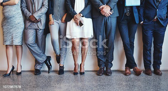 Shot of a group of unrecognizable businesspeople waiting in line for their interviews inside of a office during the day