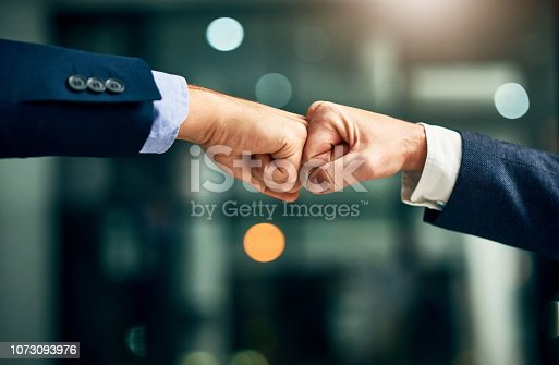 Cropped shot of two unrecognizable businessmen fist bumping in an office