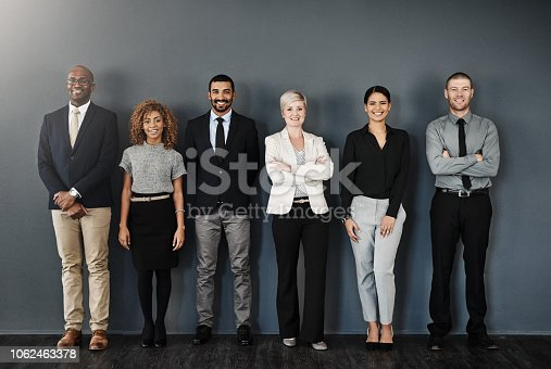 Studio portrait of a group of businesspeople posing against a dark background