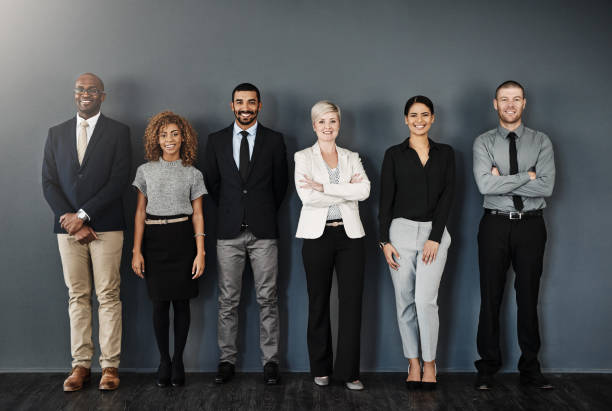 Ready to make success happen Studio portrait of a group of businesspeople posing against a dark background office photos stock pictures, royalty-free photos & images