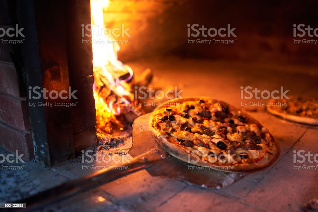 ready to pick up pizza oven with fire on blade. stock photo