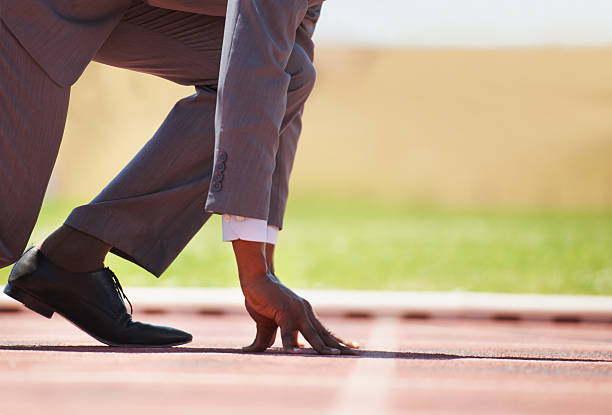Ready to produce the results A businessman on a track ready to run track starting block stock pictures, royalty-free photos & images