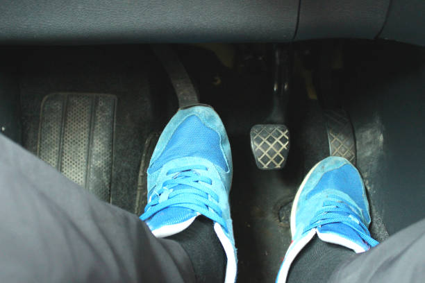 Ready to shift gear. Legs on car pedals, ready for shifting gear. vehicle clutch stock pictures, royalty-free photos & images