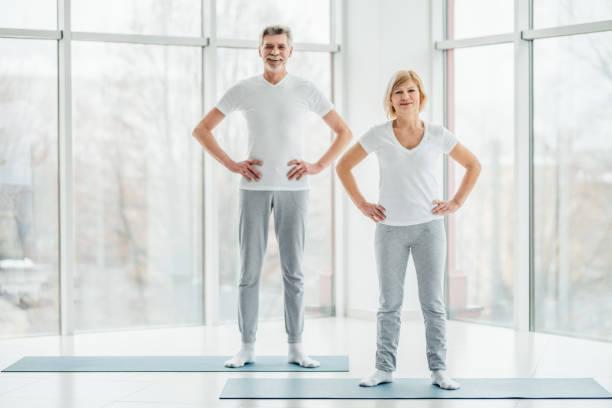 準備開始培訓。美麗的老年夫婦站在寬敞的白色健身室前的運動會議。 - 異性情侶 個照片及圖片檔