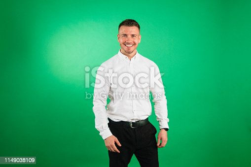 Man standing against a green studio background dressed smartly, smiling at the camera.
