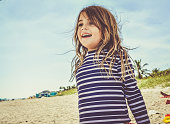 Cute little girl in a swim shirt, rash guard, on a beach, full of happy smiles in a candid vintage styled photograph