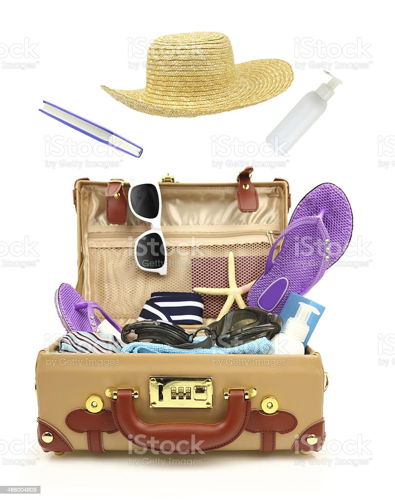 Ready to travel open suitcase with summer equipment isolated stock photo