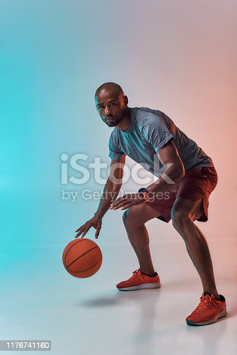 Ready to win. Full length of confident young african man in sports clothing playing basketball while standing against colorful background. Active lifestyle. Professional sport. Web banner