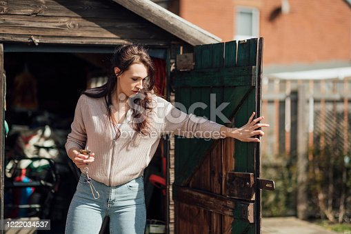 Woman opening a shed door in her garden, holding a padlock where she has unlocked it.
