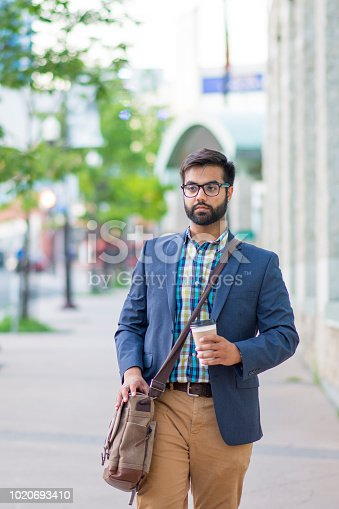 Handsome young Indian business man walking down the sidewalk of a busy city street drinking a coffee. He is wearing a blue blazer, collared shirt and hipster glasses.