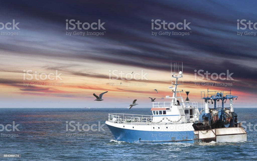 Ready to work, small fisherman ship toward the sea early in the morning, France, Guilvinec stock photo