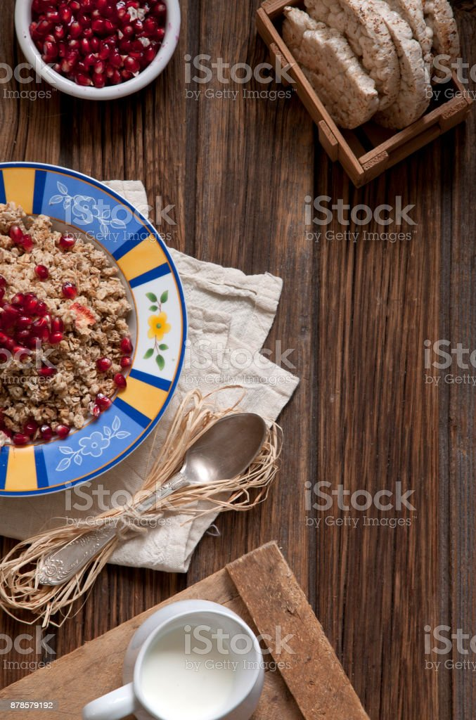 Ready-made healthy breakfast - muesli or granola with pomegranate seeds and fresh natural yoghurt on rustic wooden background, top view stock photo