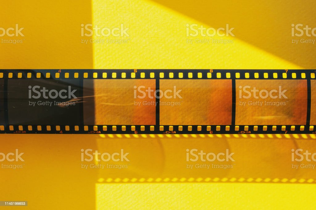 real 35mm film or movie strip with empty frames or cells on yellow background with sunlight real 35mm film strip on yellow background 35mm Film Motion Picture Camera Stock Photo