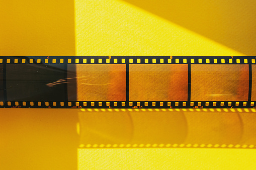 Real 35mm Film Or Movie Strip With Empty Frames Or Cells On Yellow Background With Sunlight Stock Photo - Download Image Now