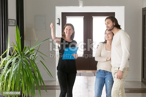 Three person standing in hallway. Smiling real estate agent, realtor showing property house for sale or tenant to young happy married couple. New home, moving and realestate loan and mortgage concept