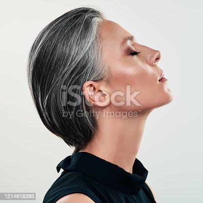 Studio shot of a beautiful mature woman posing against a grey background