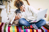 real best friends cheerful woman working at laptop on the terrace at home while hug her best love and friends  smiling dog pug sitting at his left. colorful and enjoyed concept image for alternative couple