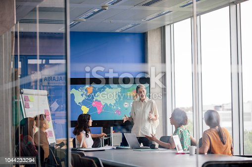A young woman is giving presentation speech in an open plan, bright, modern office. Large windows, flood natural light onto the realistic meeting. Focus technique and layers are used to create, a caught in the moment scenario. The animated speaker is enthusiastic and positive in her body language. These confident women listen eagerly, and pose questions to the standing head of the board room. The colour blue is dominant in this image.