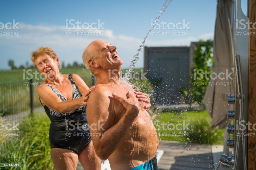 Real Bodies, seniors in swimming outfit under garden shower having fun стоковое фото