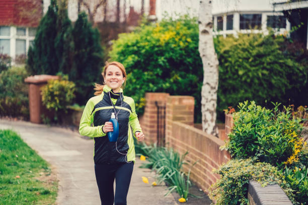 reale körper frau joggen in uk - motivationsmusik stock-fotos und bilder