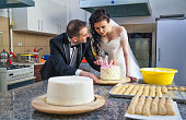 Newlywed couple mixing dough, whisking cream and preparing her wedding cake in kitchen