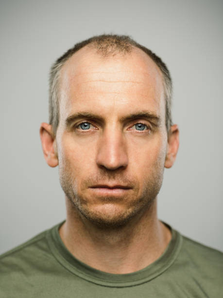 Real caucasian man with blank expression Close up portrait of mature adult adult caucasian man with blank expression against gray background. Vertical shot of real canadian man staring in studio with short balding hair and blue eyes. Photography from a DSLR camera. Sharp focus on eyes. fine art portrait stock pictures, royalty-free photos & images