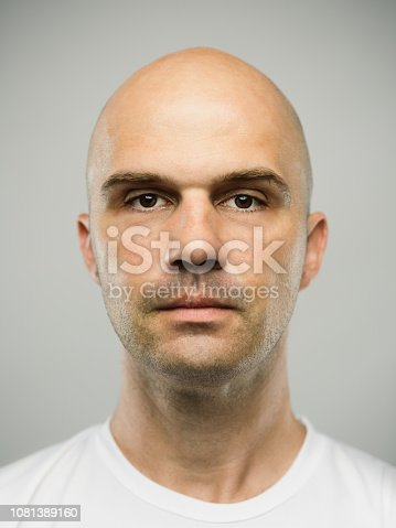 Close up portrait of mid adult adult caucasian man with blank expression against gray background. Vertical shot of real serbian man staring in studio with bald shaved head and brown eyes. Photography from a DSLR camera. Sharp focus on eyes.