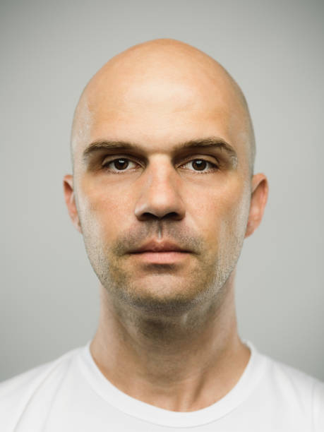 Real caucasian man with blank expression Close up portrait of mid adult adult caucasian man with blank expression against gray background. Vertical shot of real serbian man staring in studio with bald shaved head and brown eyes. Photography from a DSLR camera. Sharp focus on eyes. shaved head stock pictures, royalty-free photos & images