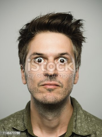 Close up portrait of young adult man with sursprised expression looking at camera against gray white background. Vertical shot of caucasian real people shocked in studio with brown hair and modern spiky haircut. Photography from a DSLR camera. Sharp focus on eyes.