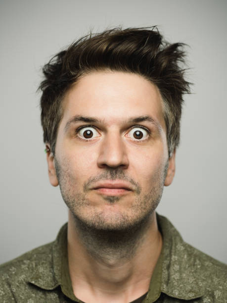 Real caucasian man with surprised expression looking at camera Close up portrait of young adult man with sursprised expression looking at camera against gray white background. Vertical shot of caucasian real people shocked in studio with brown hair and modern spiky haircut. Photography from a DSLR camera. Sharp focus on eyes. bad news stock pictures, royalty-free photos & images