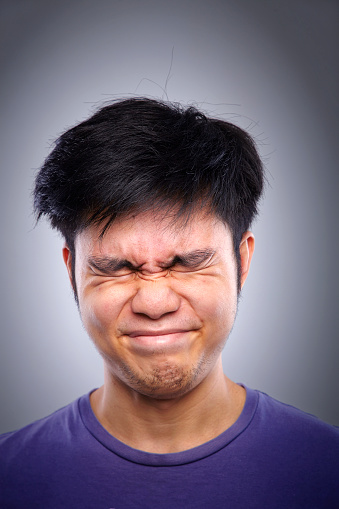 Close up portrait of asian man with grimacing with eyes closed against white gray background.