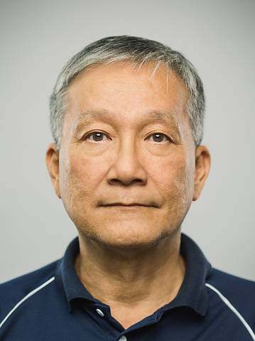 Close up portrait of senior asian man with blank expression against gray background. Vertical shot of real chinese man staring in studio with gray hair. Photography from a DSLR camera. Sharp focus on eyes.