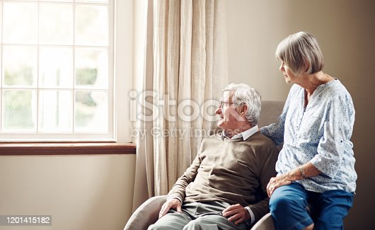 Shot of a senior couple looking thoughtfully out of a window at home