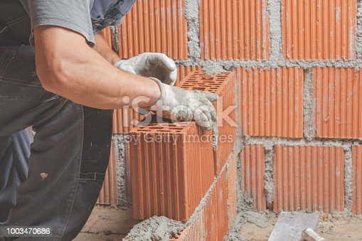 istock Real construction worker bricklaying the wall indoors. 1003470686