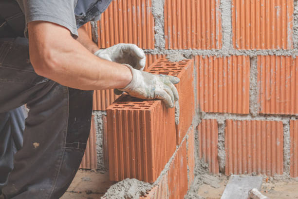 Real construction worker bricklaying the wall indoors. stock photo