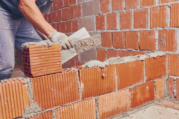 Echter Bauarbeiter mauert die Wand drinnen. – Foto