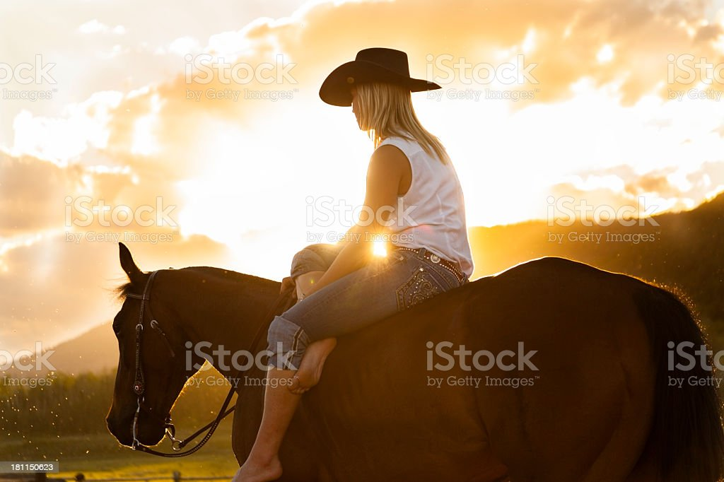 Real Cowboys:  Female wrangler relaxing with her horse.  Sunset. stock photo