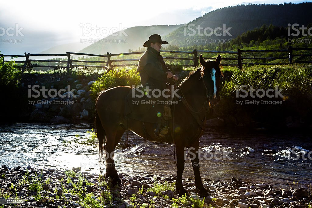 Real Cowboys: Man riding bay horse along ranch stream. stock photo