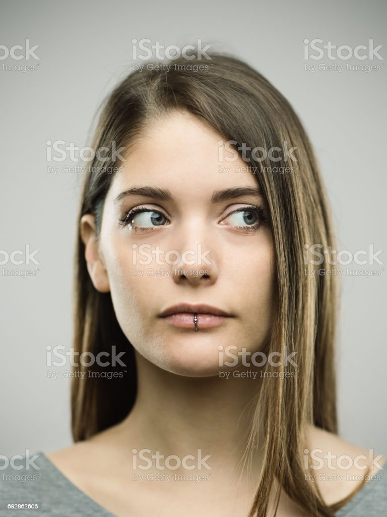 Real curious young woman studio portrait stock photo