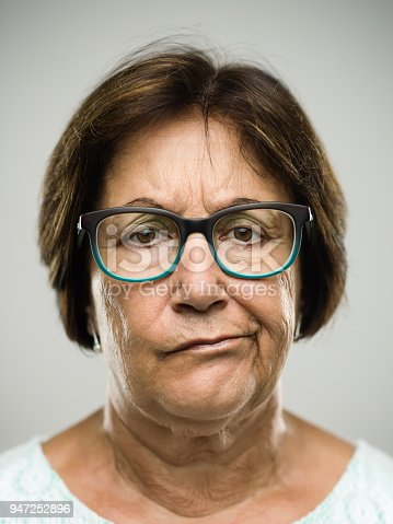 Close up portrait of hispanic mature woman with bored expression against white background. Vertical shot of real senior woman in studio. Short brown hair and modern glasses. Photography from a DSLR camera. Sharp focus on eyes.