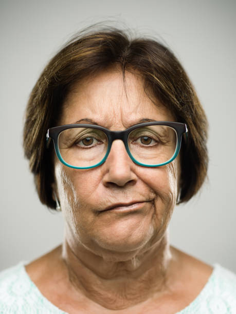Real displeased senior woman portrait Close up portrait of hispanic mature woman with bored expression against white background. Vertical shot of real senior woman in studio. Short brown hair and modern glasses. Photography from a DSLR camera. Sharp focus on eyes. agitation stock pictures, royalty-free photos & images