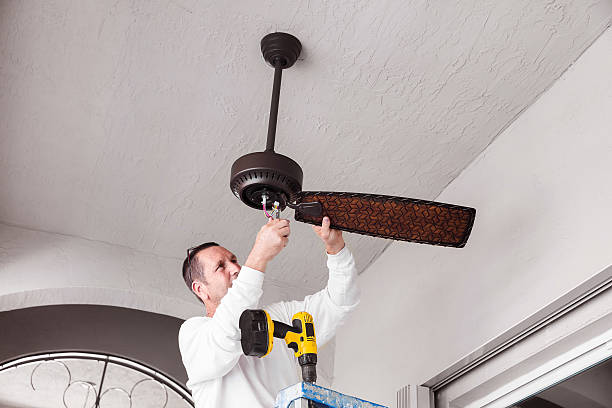 Real Electrician Hanging a Ceiling Fan A photograph of an electricians hanging a ceiling fan. The man is holding wires in his hand. He is wearing a long sleeved white shirt and is fixing the fan. He has a drill sitting on a ladder. The walls are white and the fan is brown and dark brown.  ceiling fan stock pictures, royalty-free photos & images