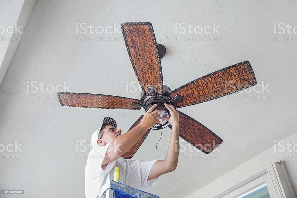 Real Electrician Hanging a Ceiling Fan  rr stock photo