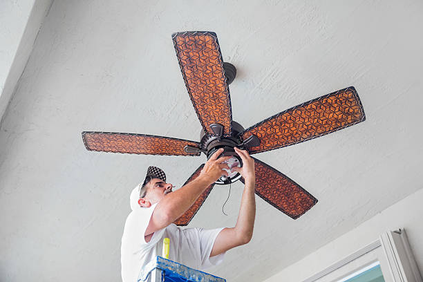 Real Electrician Hanging a Ceiling Fan  rr A real electrician stands on a ladder while finishing hanging a ceiling fan.  rr ceiling fan stock pictures, royalty-free photos & images