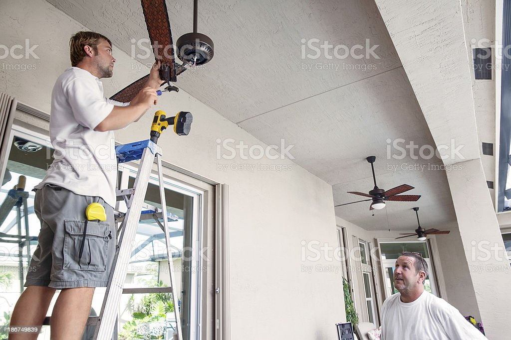 Real Electrician hanging ceiling fans royalty-free stock photo