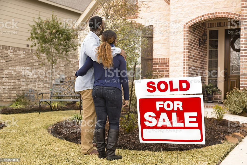 Real Estate: African descent couple admires new home. Happy homeowners! stock photo