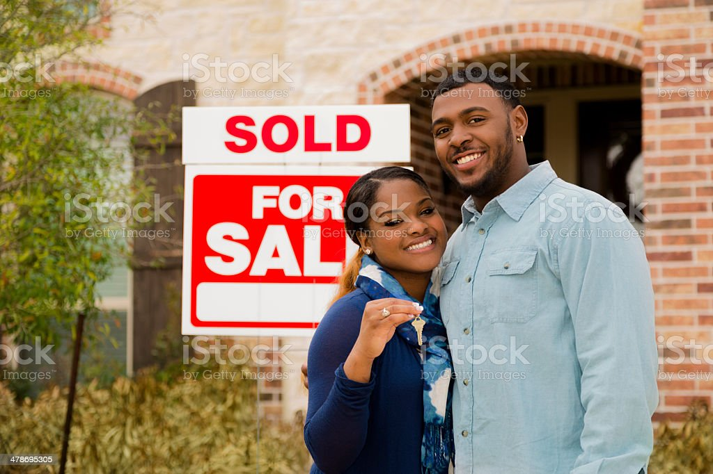 Real Estate: African descent couple buys first home. House key. stock photo